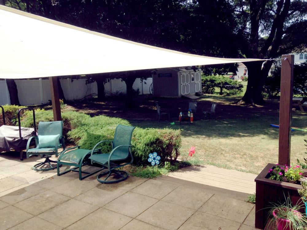 Backyard with sun shade sail over patio and wooden sun shade sail posts