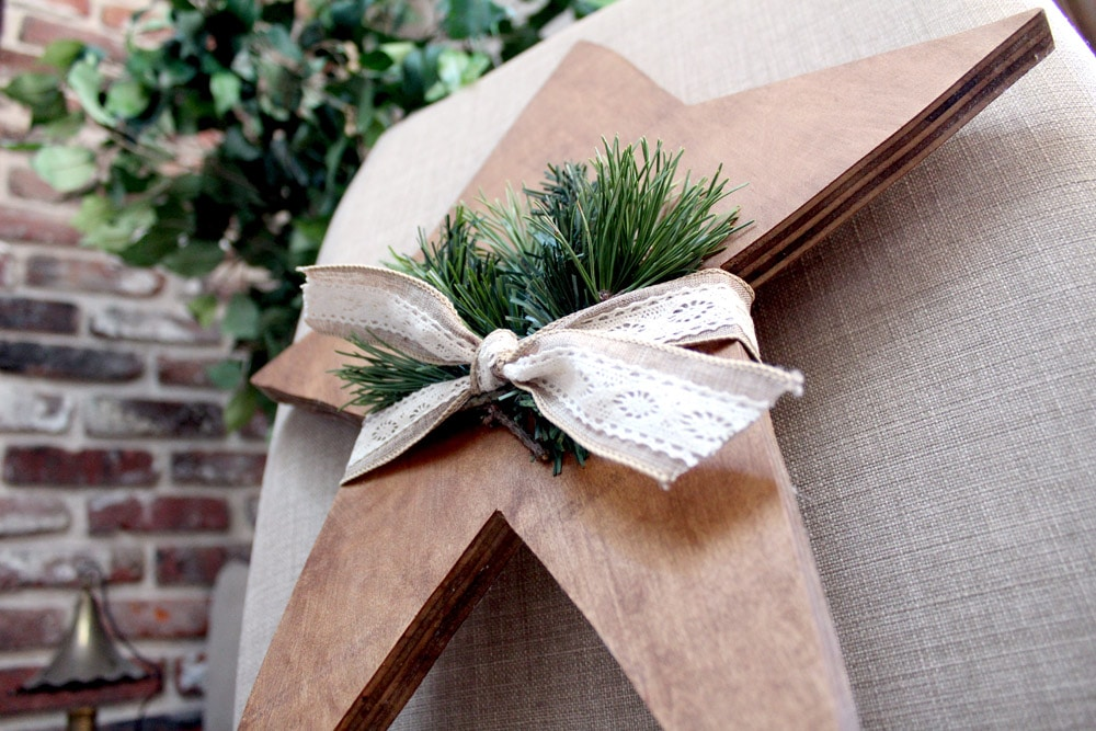 Wooden Christmas star with ribbon and greenery ready to hang on the door